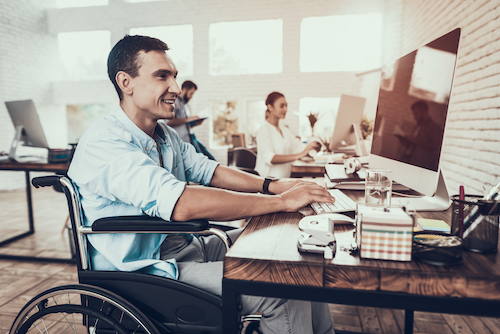 A man in business casual clothing sits in a wheelchair at a desk, typing on a keyboard, with a large iMac computer. He's in a bright, trendy, open office space, with several coworkers pictured in the background.